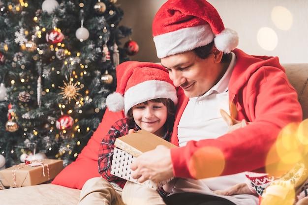 Семья в шляпе санты, отец и сын открывают рождественский подарок дома Premium Фотографии
