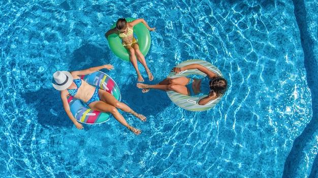 上からスイミングプール空中ドローンビューで家族、幸せな母と子供たちはインフレータブルリングドーナツで泳ぐし、家族での休暇、リゾートの熱帯の休日に水で楽しい時を過す Premium写真