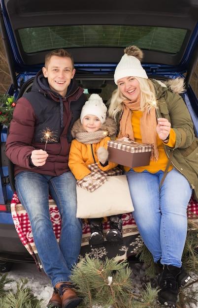 Семья в машине празднует рождество на улице зимой Premium Фотографии