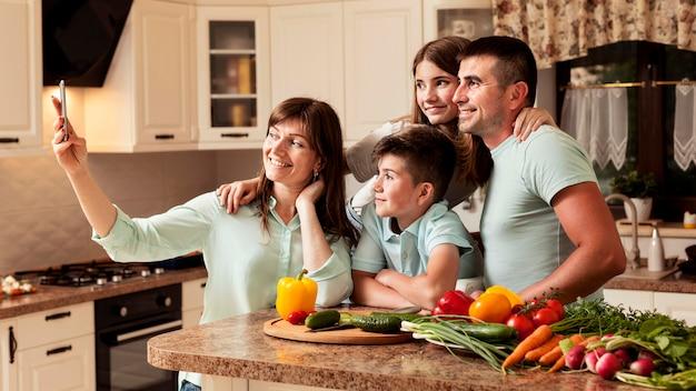 Семья на кухне, принимая селфи Premium Фотографии