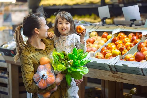 Семья в супермаркете. красивая молодая мама и ее маленькая дочь улыбаются и покупают еду. концепция здорового питания. урожай Бесплатные Фотографии