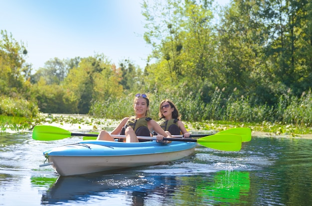 Family kayaking, mother and daughter paddling in kayak on river canoe tour having fun, active autumn weekend and vacation with children, fitness concept Premium Photo