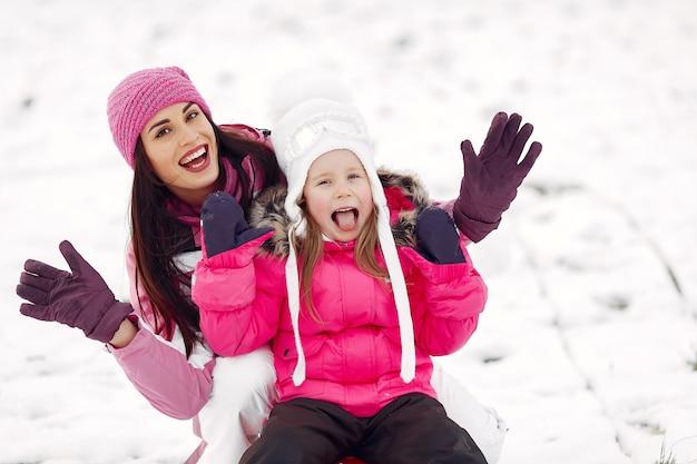 Famiglia in cappelli invernali lavorati a maglia in vacanza di natale in famiglia. donna e bambina in un parco. persone che giocano con la slitta. Foto Gratuite
