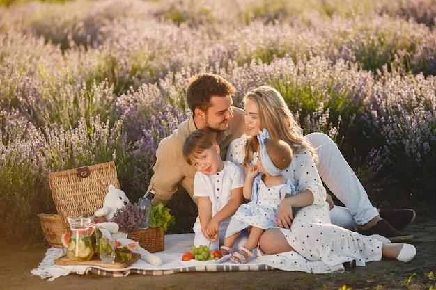 Famiglia sul campo di lavanda. persone a un picnic. la madre con i bambini mangia la frutta. Foto Gratuite