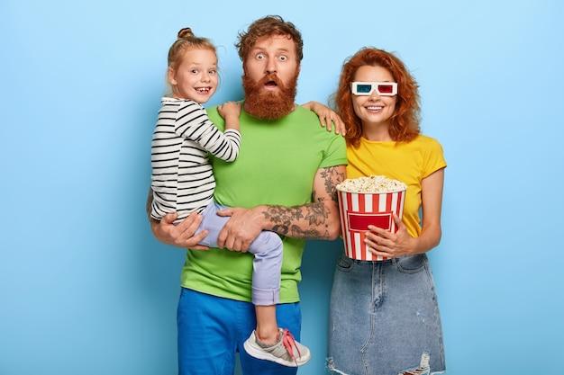 가족, 레저, 엔터테인먼트 개념. 무서워하는 아버지, 웃는 어머니 및 기쁜 딸이 스릴러 또는 공포 영화를 본다. 무료 사진