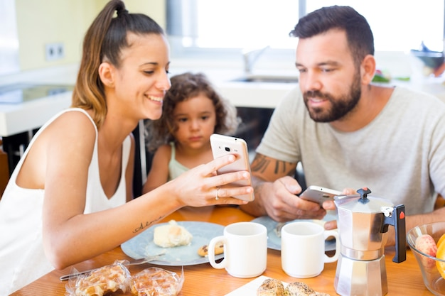 Family looking at mobile phone screen during breakfast Free Photo