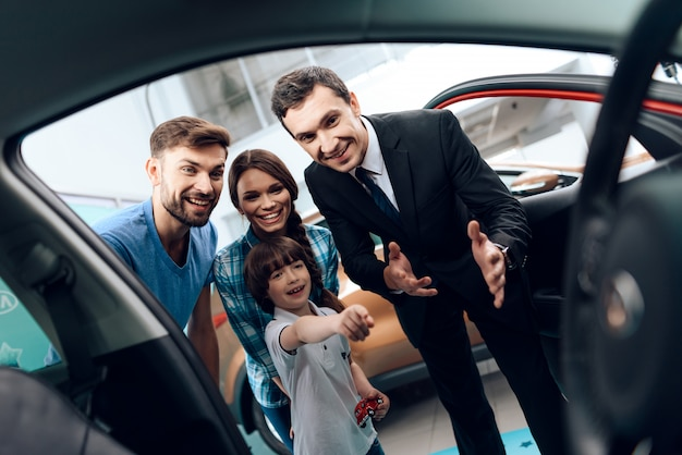 The family looks inside the car and smiles. Premium Photo