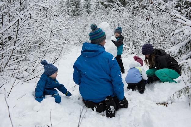雪の日に雪だるまを作る家族 無料写真