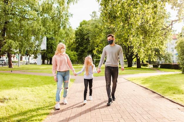 布製のフェイスマスクを着て公園を歩く家族。 Premium写真