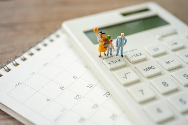 Family miniature people pay queue annual income (tax) for the year on calculator. Premium Photo