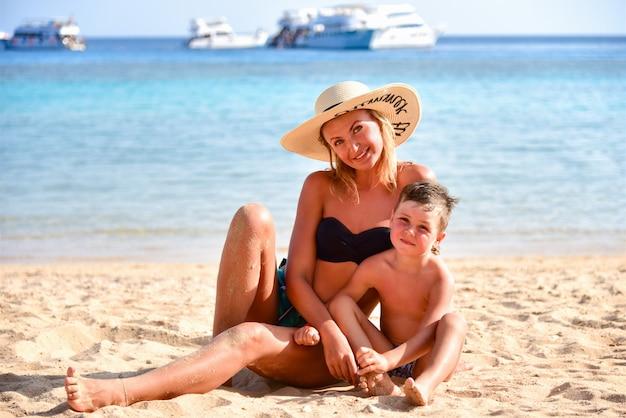 家族のお母さんと息子の砂で遊んで、ビーチで笑って Premium写真