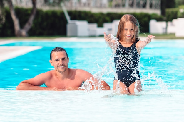 Family of mom and little daughter enjoying summer vacation in luxury swimming pool Premium Photo