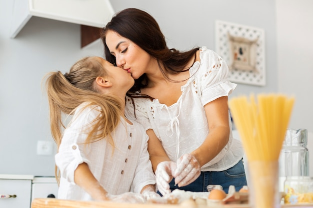 Family moments mother and daughter kisses Free Photo