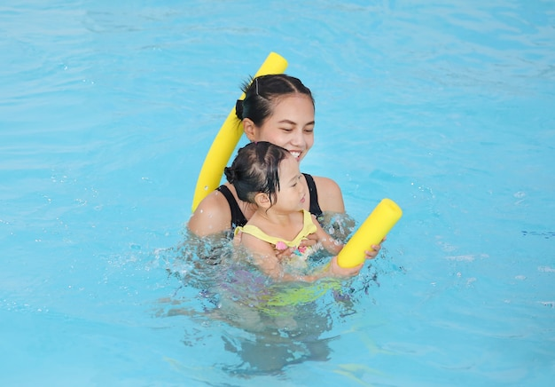 Family of mother teaching kid girl in swimming pool with noodle foam Premium Photo