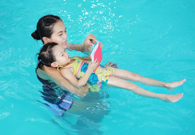 Family of mother teaching kid in swimming pool Premium Photo