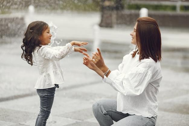 市の噴水の近くの家族。水で遊ぶ笑いを持つ母。 無料写真