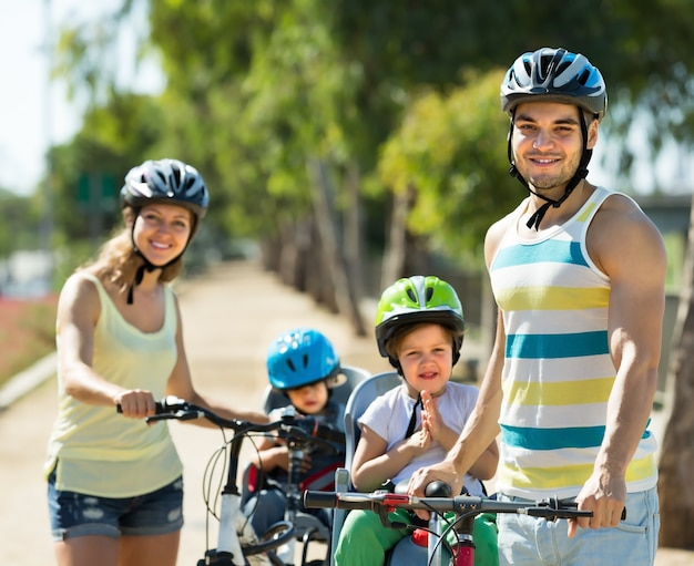 Family of four cycling on street Free Photo