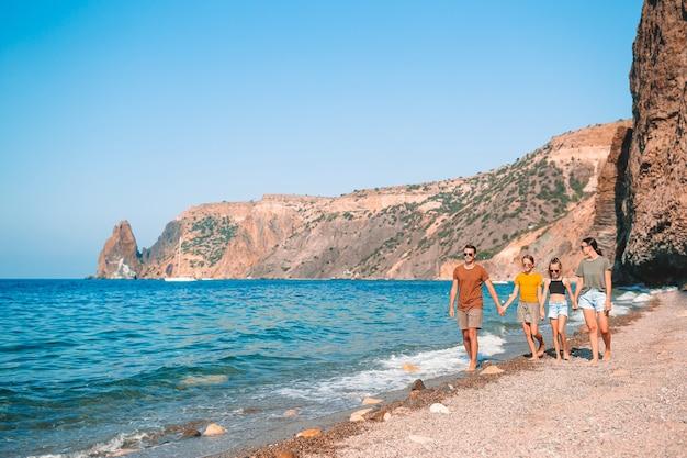 Семья из четырех человек, весело проводящих время на пляже Premium Фотографии