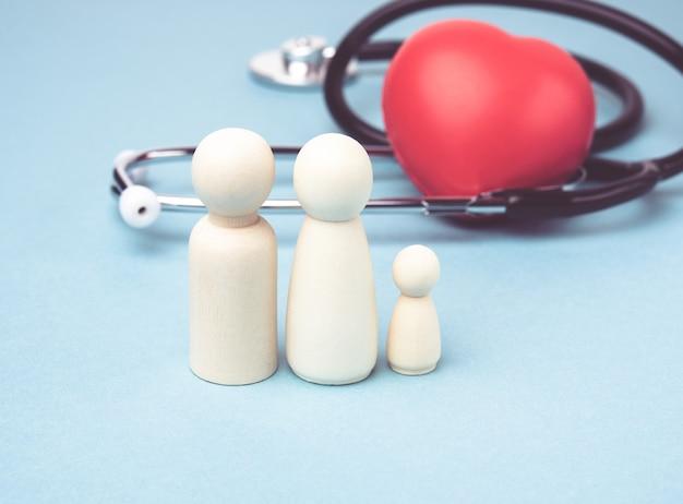 Семья деревянных фигур мужчин на фоне красного сердца и стетоскопа, концепция медицинского страхования, крупным планом Premium Фотографии