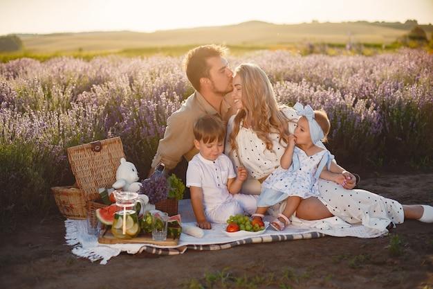 ラベンダー畑の家族。ピクニックの人々。子供を持つ母は果物を食べる。 無料写真