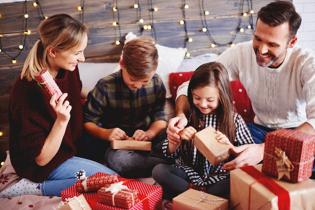 Famiglia che apre i regali di natale nel letto Foto Gratuite