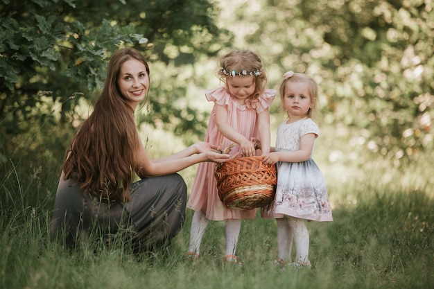 Family photo mom with daughters in the park. photo of young mother with two cute kids outdoors in spring time, beautiful woman with daughter having fun Premium Photo