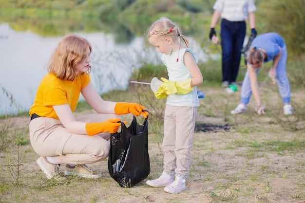 Семья собирает мусор на пляже летом Premium Фотографии