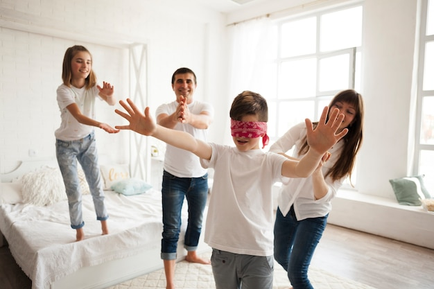 Family playing blind man's buff in bedroom Free Photo