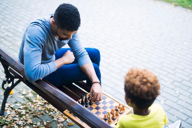 公園のベンチでチェスゲームをしている家族 無料写真