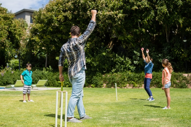 Family playing cricket in park Premium Photo