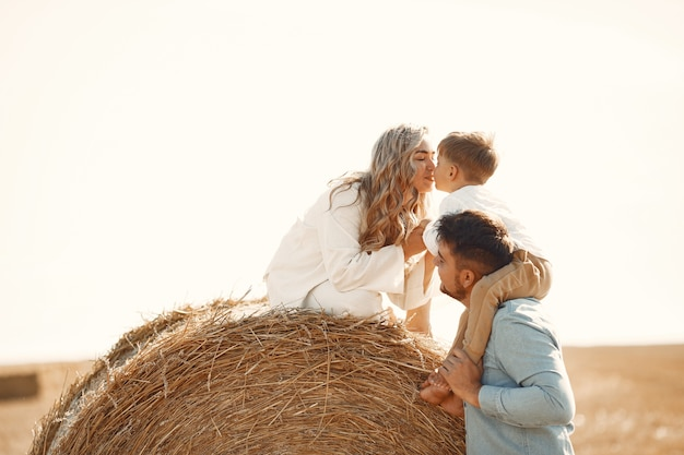 Семья играет с маленьким сыном в пшеничном поле на закате. концепция летнего отдыха. семья, проводящая время вместе на природе. Бесплатные Фотографии