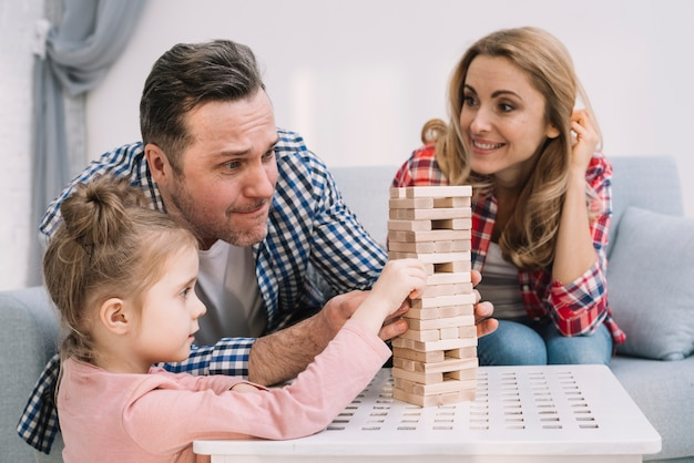 Family playing with block wooden game on table in living room Free Photo