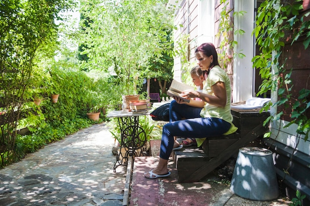 Family on porch reading book Free Photo