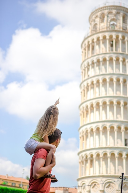 Family portrait background the learning tower. pisa - travel to famous places in europe. Premium Photo