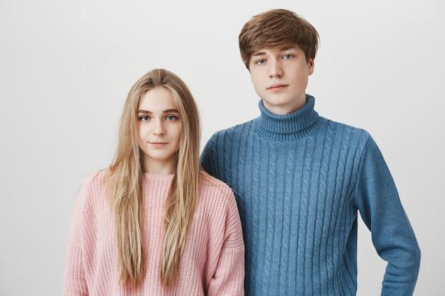 Ritratto di famiglia di giovani coppie caucasiche in maglioni. il ragazzo biondo e la ragazza con gli occhi blu guardano con espressioni calme e compiaciute Foto Gratuite