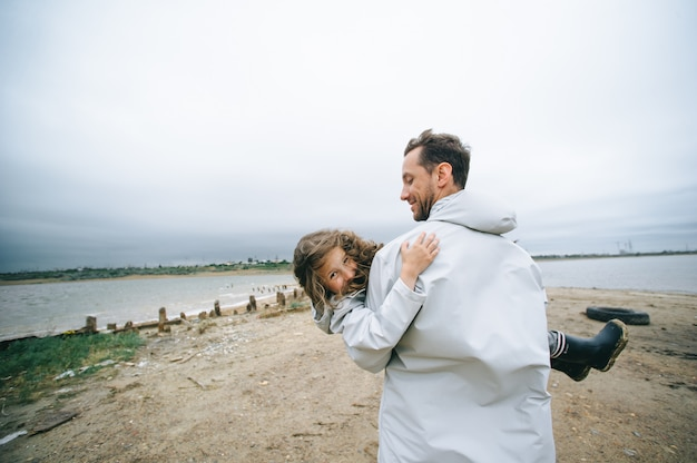 Family portrait of dad and dauther in raincoat near the sea Premium Photo