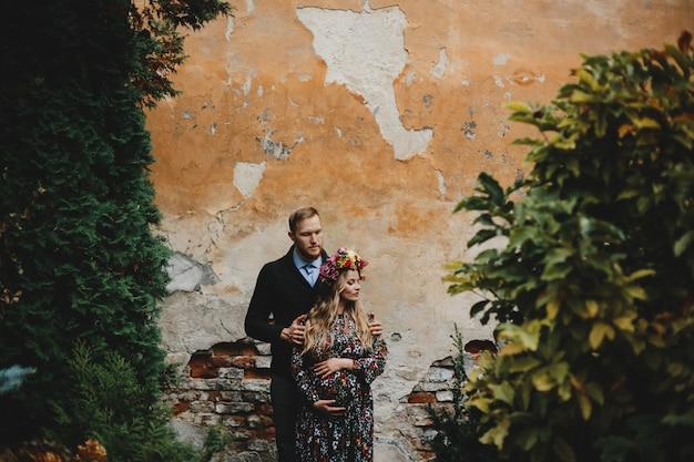 Family portrait, expacting couple. man hugs tender pregnant woman Free Photo