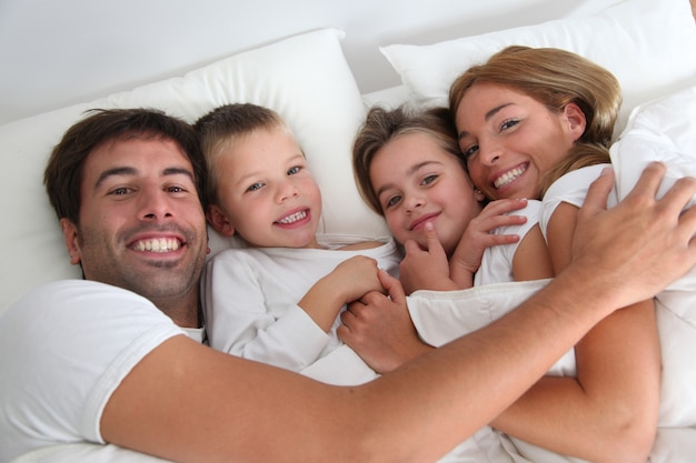 Family portrait laying in bed Premium Photo