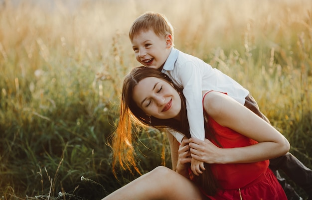 Family portrait, nature. charming mom and son play on the lawn b Free Photo