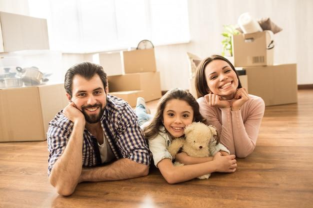 Семейный портрет трех человек, лежащих на полу. мужчина, женщина и их дочь выглядят бодрыми и счастливыми. за ними много коробок. Premium Фотографии
