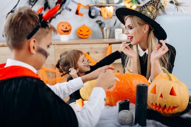 Семья готовится к празднику хэллоуин и весело проводит время. helloween Premium Фотографии