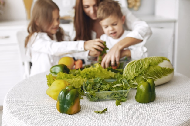 Family preparing a salad in a kitchen Free Photo