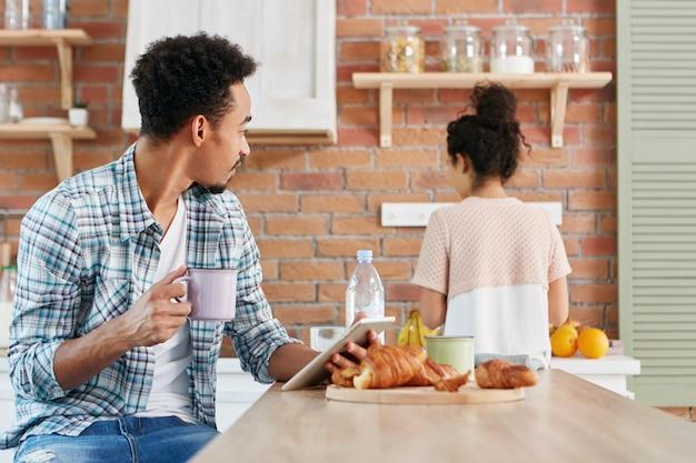 家族関係、日常的なコンセプト。混血の黒い肌のアフロアメリカンの男性がオンラインコミュニケーションにタブレットを使用 無料写真