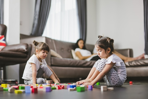 Family sad girl sitting on the floor , her sister playing the toys and mother looking her daughters together. Premium Photo