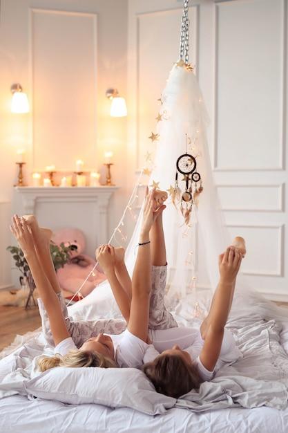 家族のシーン。ベッドで幸せな母と娘 無料写真