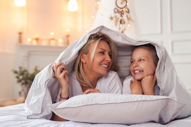 Семейная сцена. счастливая мать и дочь в постели Бесплатные Фотографии