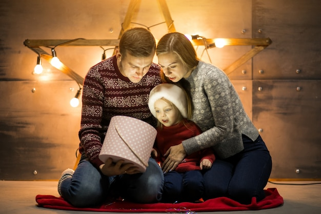 Family sitting by the christmas tree with little daughter packing gifts Free Photo