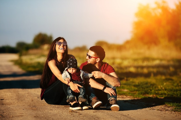 Family sitting on an dirt road with a baby Free Photo