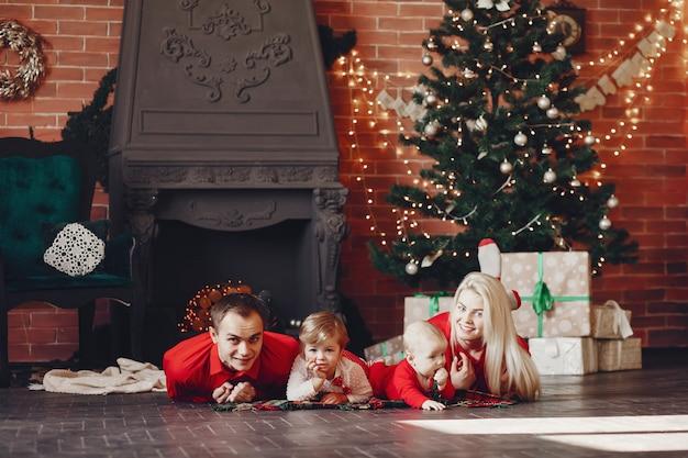 Family sitting at home near christmas tree Free Photo