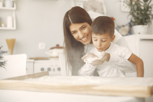 Family sitting in a kitchen and cook the dough for cookies Free Photo